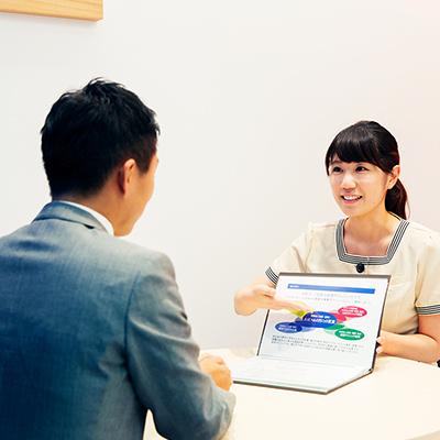 患者様に資料を見せながら治療法を説明するスタッフの女性のイメージ