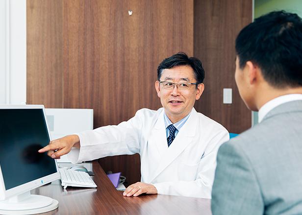 患者様に向かいPCを指さしながら説明するドクター