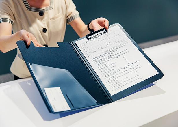 受付で問診票を差し出すイメージ