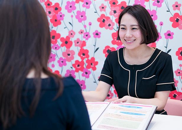 患者様に資料を見せながら治療の流れを説明するスタッフの女性のイメージ